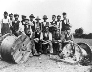 A cable crew take a break behind drums of wire during the roll-out of the Rural Electrification Scheme