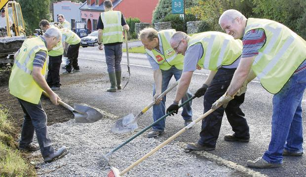 UNITED: Some of the 40 local volunteers level council-supplied gravel to construct the 2km of footpath through the village of Ogonnelloe, Co Clare