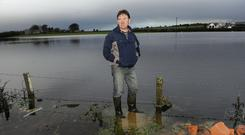 Heartache: Cllr Peter Roche beside a flooded field at the home of farmer Joe Fahy in Killererin, Co Galway. Photo: Ray Ryan.
