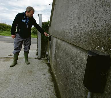 Keith Daly of Total Security systems points out the double sensor system that he has installed on Andrew's farm