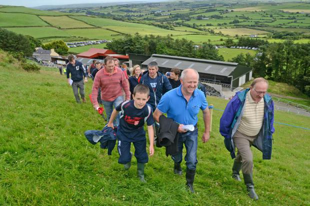 Diarmuid McCarthy and his son John, and Norman Perrott (right) from Barryroe making their way up a steep hill 700 feet above sea level during the recent Carbery/Teagasc farm walk on the lands of Tim and Breda Hurley, Caherbeg, Rosscarbery who were the Carbery milk quality award winners for 2015. Photo: Denis Boyle