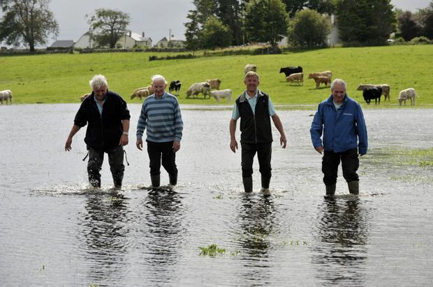 Jarlath Farrell, Dom Dunleavy, Sonny Jennings and John Keane wade through the floodwater at Barbersfort, Cahergal, Co Galway after the River Grange burst its banks last summer. Photo: Ray Ryan.