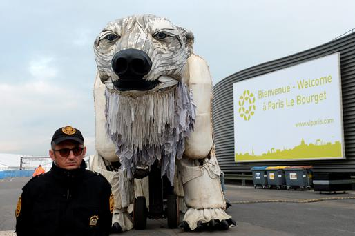 A UN security guard stands beside Greenpeace giant polar bear puppet 'Aurora' which the organisation placed outside climate change conference in Paris. Photo: AFP/Getty Images
