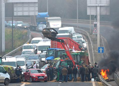 French farmers demonstrate and block the access to Le Mans as they protest against falling prices of dairy and meat products on January 21, 2016, in Le Mans, north western France. Photo: AFP