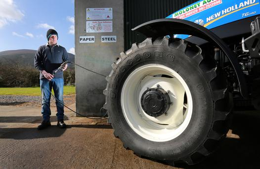 Thomas Moloney pumps a tractor wheel on his yard in Clogheen, Co Tipperary.