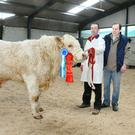 Gerard O'Keeffe,Grange, Knocklong, Co Limerick with his Charolais bull, Grangwood Limerick, reserve champion at the Irish Charolais Show and Sale at Tullamore which sold for the top price of €5,150, and Gene McCann, judge.