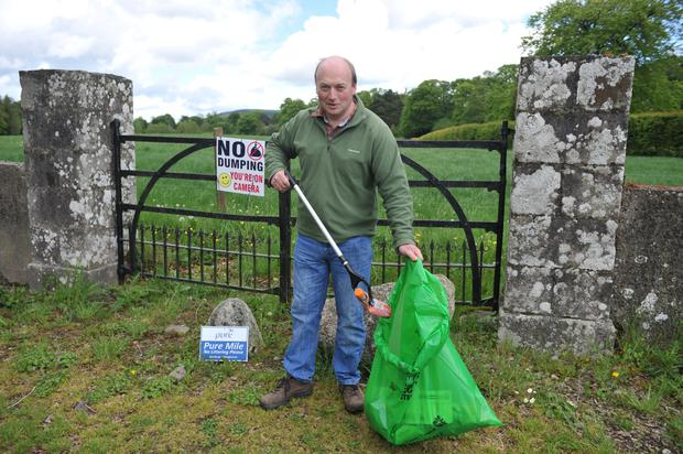 William Grogan cleaning some of the rubbish dumped on his farm in Co Wicklow.
