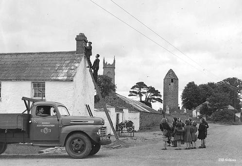 Two workers on a ladder at a house in Dromiskin, Co Louth are watched by schoolchildren during the hooking up of electricity for the village