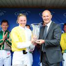 Alice Kavanagh receives the winner's trophy from Curragh Racecourse CEO Derek McGrath after her win at the Kildare track in July