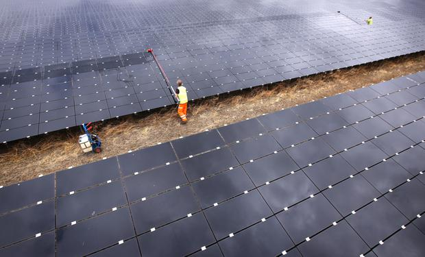 A workman cleans panels at Landmead solar farm near Abingdon, England. The 46 megawatt capacity installation was the largest in the UK when it was completed in 2014. (Photo by Peter Macdiarmid/Getty Images)