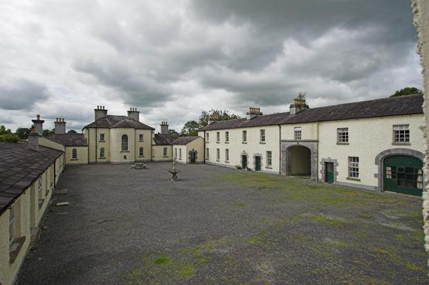 The courtyard is flanked by two single-storey houses and a two-storey house