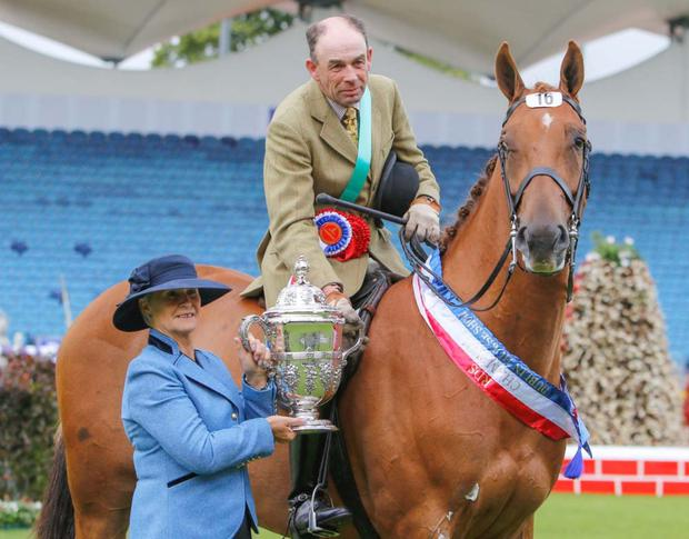 Gillian Kyle presents the Samuel Ussher Roberts Perpetual Cup for champion lightweight hunter to Kieran Ryan, rider of Maria Melvin's Glenkeeran Dance Inthedeep