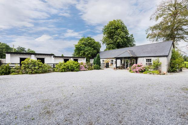 The outbuildings include a spacious cottage and stable block with 10 boxes