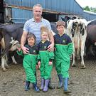 Leddy at work in the milking parlour on his farm near Belturbet, Co Cavan; (below) Anthony with his children Joshua, Jessica and Aiden PhotoS: LORRAINE TEEVAN