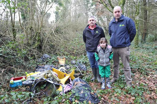 Trevor Smith (left) with his daughter Neeva (7) and Thomas Cooney, national environment and rural affairs chairman, IFA, on land he farms in Co Cavan. Trevor has a significant problem with rubbish of all kinds being dumped on his land. Photo: Lorraine Teevan