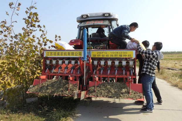 Staff members taking part in the experiment on automated farming machinery load fertilizer onto an automated tractor near a field in Xinghua, Jiangsu province, China October 30, 2018. Picture taken October 30, 2018. REUTERS/Hallie Gu