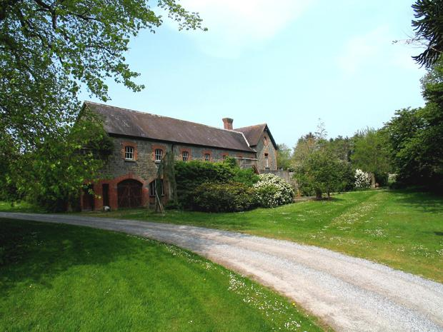 The extensive outbuildings include the original coach house and a five-bay shed for a wood-chip heating system