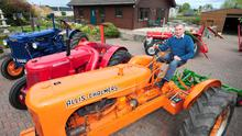 George Farrar with some of the vintage tractors he has restored to their former glory