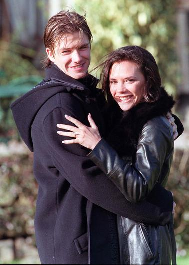 """British footballer David Beckham and fiance singer from the """"Spice Girls"""" Victoria Adams pose for photographers outside their hotel after the announcement of their engagement on January 25, 1998 in Chester, United Kingdom. (Photo by Dave Hogan/Getty Images)"""