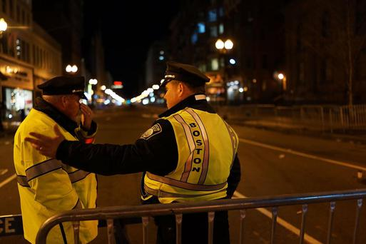 Boston Police stand near the scene of a twin bombing at the Boston Marathon, on April 16, 2013 in Boston, Massachusetts. Three people are confirmed dead and at least 141 injured after the explosions went off near the finish line of the marathon.