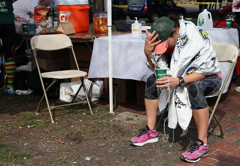 A runner sits near Kenmore Square after two bombs exploded during the 117th Boston Marathon on April 15, 2013 in Boston, Massachusetts. Two people are confirmed dead and at least 23 injured after two explosions went off near the finish line to the marathon.