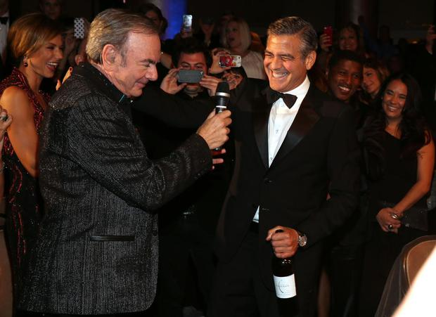 Singer Neil Diamond (L) and actor George Clooney perform during the 26th Anniversary Carousel Of Hope Ball presented by Mercedes-Benz at The Beverly Hilton Hotel on October 20, 2012 in Beverly Hills, California.