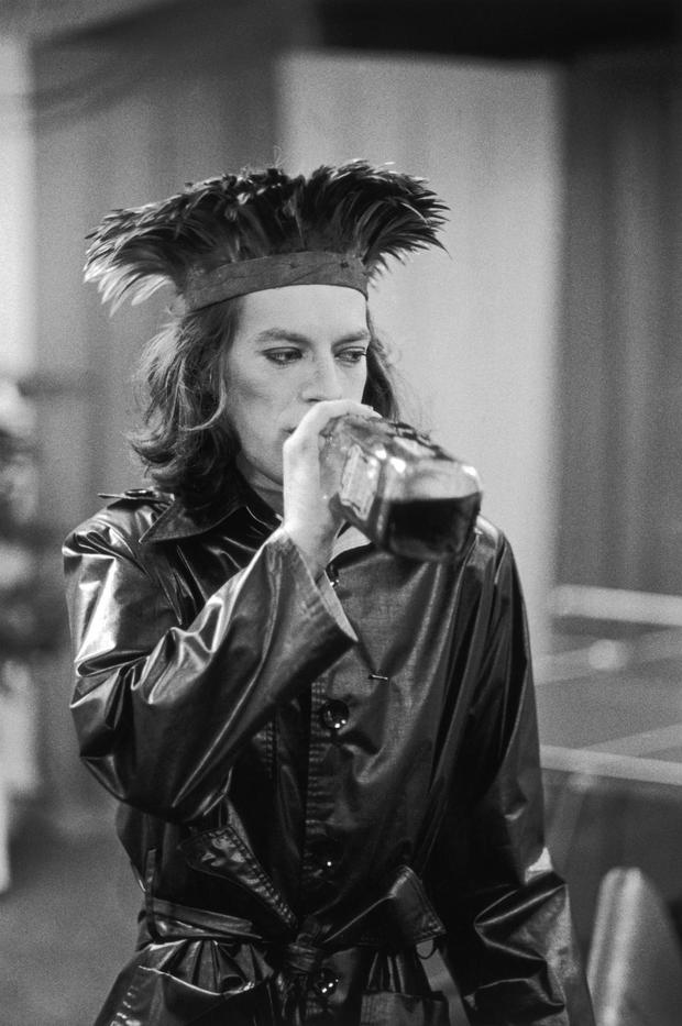 Mick Jagger, in a plastic mac and feather headdress, takes a swig of bourbon backstage during the Rolling Stones' 1975 Tour of the Americas. (Photo by Christopher Simon Sykes/Hulton Archive/Getty Images)