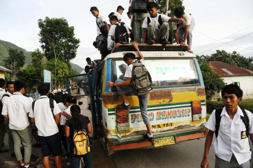 SAMOSIR, SUMATRA, INDONESIA - SEPTEMBER 18: Indonesian students travel atop an overloaded bus on a school run in Simanindo Regency on September 18, 2013 in Samosir, Sumatra, Indonesia. Local school students put their own safety at risk and ignore the road rules to get cheap transport. Students can pay less than US $1 for a distance up to 50 km. (Photo by Robertus Pudyanto/Getty Images)