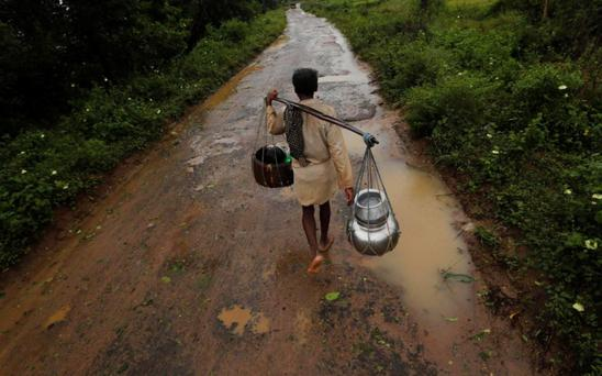 A man carrying his belongings walks towards a safer place at the village Donkuru in Srikakulam district in the southern Indian state of Andhra Pradesh October 12, 2013. Rain and wind lashed India's east coast on Saturday, forcing more than 400,000 people to flee to storm shelters as one of the country's largest cyclones closed in, threatening to cut a wide swathe of devastation through farmland and fishing hamlets. Filling most of the Bay of Bengal, Cyclone Phailin was about 200 km (124 miles) offshore by noon on Saturday, satellite images showed, and was expected to hit land by nightfall. REUTERS/Adnan Abidi (INDIA)