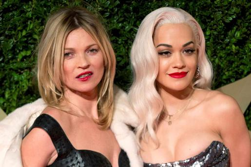 Model Kate Moss and singer Rita Ora (R) pose up a storm at the British Fashion Awards. REUTERS/Neil Hall