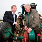 Taoiseach Enda Kenny with Eamonn Tracey from Carlow, the current world champion in the senior tractor class, at the National Ploughing Championships in Ratheniska, Co Laois, yesterday