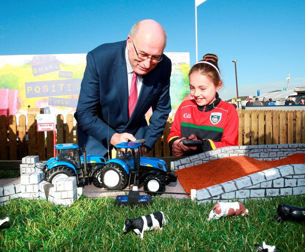 EU Commissioner for Agriculture Phil Hogan tries his hand at driving a remote-control tractor with Eva Nolan (7) from Wexford on the Macra na Feirma stand at the National Ploughing Championships yesterday