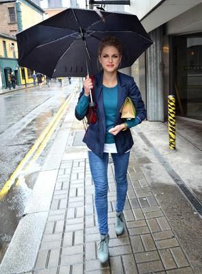 Even a massive brolly doesn't detract from her stylish combination of blazer, skinnies and boots.