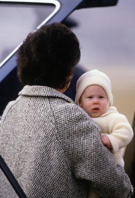 Harry is carried by his nanny on a Royal flight in 1985.