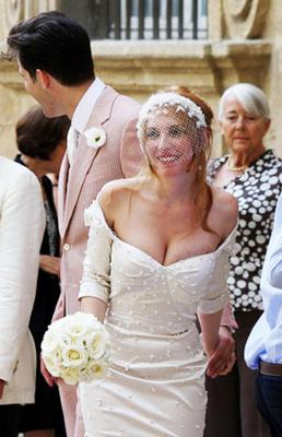 When the French singer/model Josephine de la Baume married music producer Mark Ronson in the South of France , she chose a very low cut, pearl-embroidered, off-the-shoulder Zac Posen gown with a short, cropped veil. Her groom almost outshone her in a pink suit.