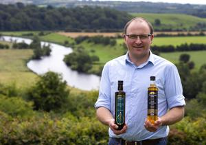 Prize crops: Jack Rodgers, manager of Newgrange Gold, holds a bottle of Camelina 'Wild Flax' oil in a field of camelina crop in Tara, Co. Meath. Photos: Damien Eagers
