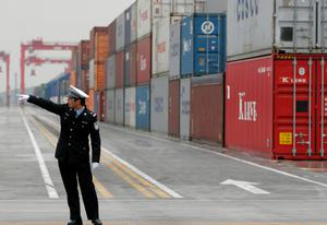YangshanPort_04 20051210 SHANGHAI,CHINA: A police officer directs traffic at the opening of the Yangshan Deep Water Port in Shanghai, China 10 December 2005. The port will give the city it's first deep water port, adding capacity to its formidable shipping infrastructure,  already Shanghai is expected to become world's largest freight port at the end of this year surpassing Singapore, according to materials provided by the Ministry of