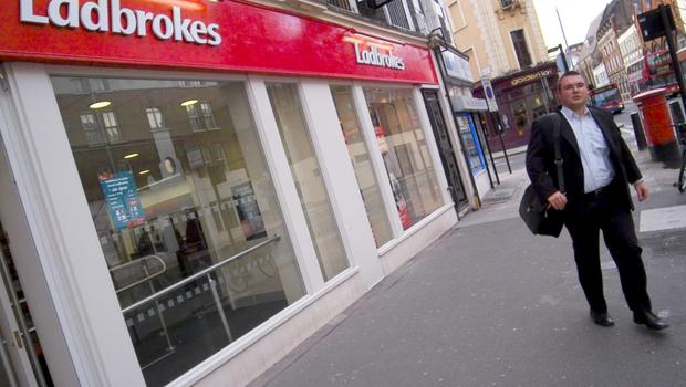 A pedestrian passes a Ladbrokes betting shop in central London, U.K., Wednesday, March 22, 2006. Photographer: Adrian Brown/Bloomberg News