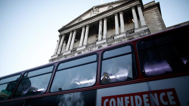 """The word """"Confidence"""" sits on an advertisement on the side of a red London bus as it passes the Bank of England in London, U.K., on Tuesday, Dec. 16, 2014. HSBC Holdings Plc and Standard Chartered Plc will probably face a tougher stress test next year as the Bank of England turns its attention to mounting risks abroad. Photographer: Simon Dawson/Bloomberg"""