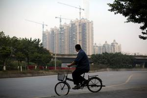 A man on a bicycle rides past a residential construction site near Canton Tower in the Haizhu district of Guangzhou, China, on Saturday, Nov. 23, 2013. Photographer: Brent Lewin/Bloomberg