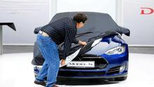 An employee covers a Tesla Model S car during the media day at the Frankfurt Motor Show (IAA) in Frankfurt, Germany, September 14, 2015. Flush with cash and confidence after years of rising sales, German carmakers are used to reaping industry-leading returns. But with Chinese demand abruptly slowing, the profit engine has begun to sputter, overshadowing the glitz of the world's biggest auto show which opens on Tuesday in Frankfurt