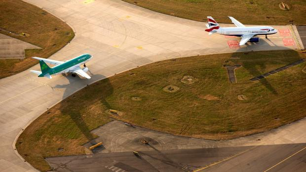 A British Airways aircraft, operated by British Airways Plc, right, and an Aer Lingus aircraft, operated by Aer Lingus Group Plc, prepare to take-off from the north runway at London Heathrow Airport, in this aerial photograph taken over London, U.K., on Tuesday, June 16, 2015. Europe's largest hub at London Heathrow, which has been operating close to capacity since the start of the decade, and rival Gatwick have been short-listed for a new runwa