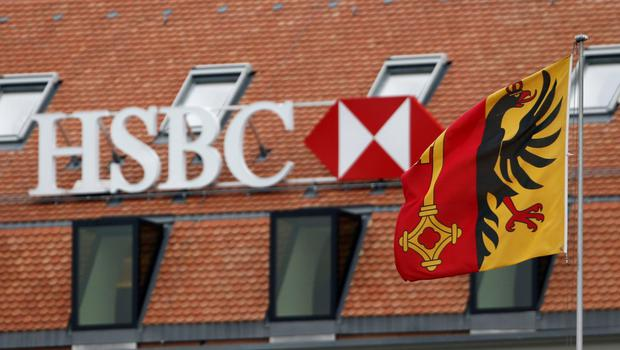 A file photo of a HSBC logo is pictured behind the flag of the canton of Geneva at a Swiss branch of the bank in Geneva February 18, 2015. HSBC said on June 4, 2015 it had agreed to pay the authorities in Geneva 40 million Swiss francs ($43 million) to settle an investigation into allegations of money laundering at its Swiss private bank. The bank said in a statement that the payment is to compensate the authorities for past organisational failings and that no criminal charges would be filed.  Picture taken February 18, 2015.  REUTERS/Denis Balibouse/File