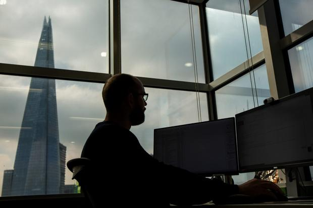 An employee looks at financial data on computer screens, in front of a view of The Shard building