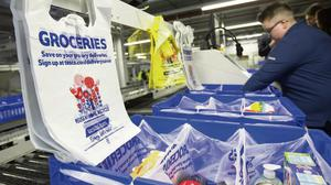 Customer orders are placed into plastic carrier bags at a Tesco on-line distribution centre. Photo: Steve Dawson/Bloomberg