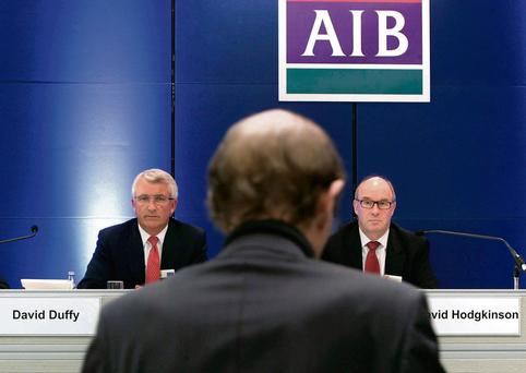 AIB chief executive David Duffy and chairman David Hodgkinson listen to shareholder Niall Murphy calling for their resignation at the bank's AGM yesterday in the Bankcentre, Ballsbridge, Dublin