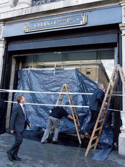 CLERYS: Workers block up a window as the department store suffered storm damage in last week's torrential downpours