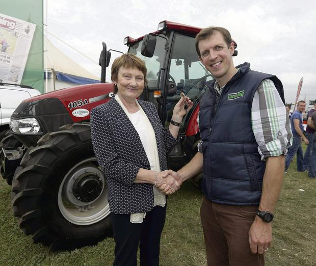 Darragh McCullough, Irish Independent Deputy farming editor presents, Elizabeth O'Reilly, from Enfield, the winner of an Irish Farming Independent competition, with the keys to a new Case IH farmall tractor at the National Ploughing Championships at Rathineska, Stradbally, Co. Laois