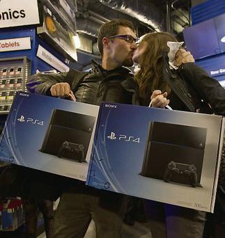 A couple kiss after buying a PlayStation 4 during its US release last week