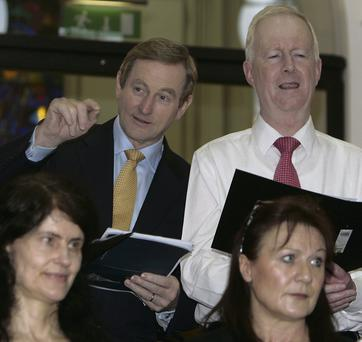 Deck the halls with boughs of holly: Taoiseach Enda Kenny and Philip Hamell, assistant secretary of the Department of the Taoiseach, with two colleagues at the annual Christmas choir concert, held at Government Buildings yesterday.